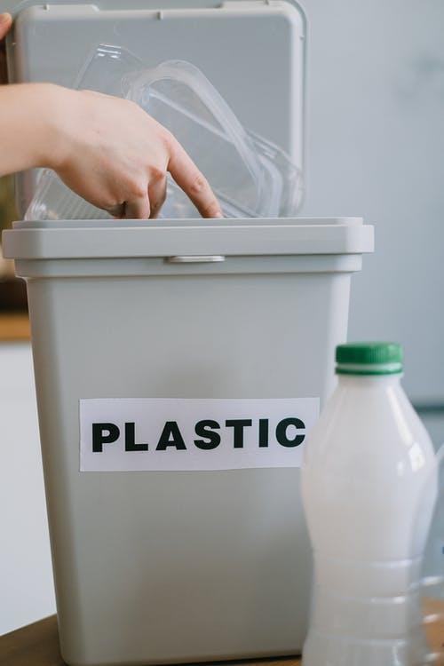 Crop anonymous person collecting plastic rubbish into bucket while cleaning home in daytime