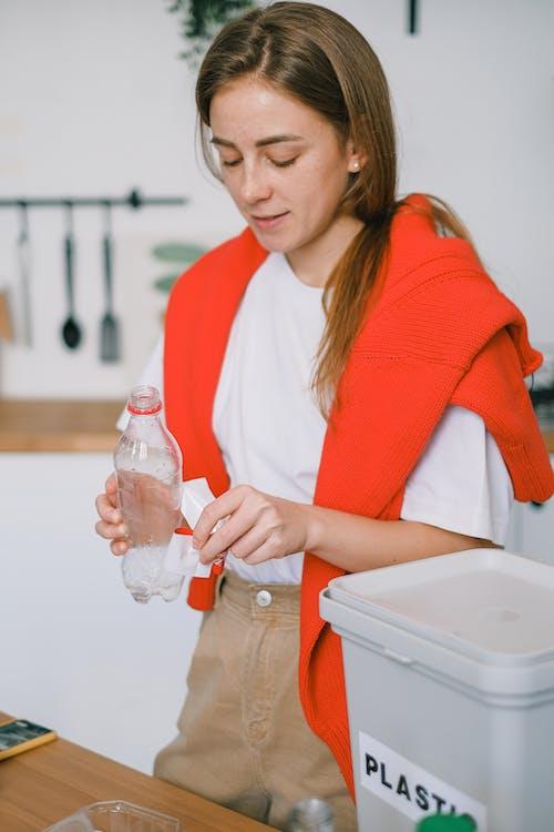 Female disposing plastic bottle into special bin