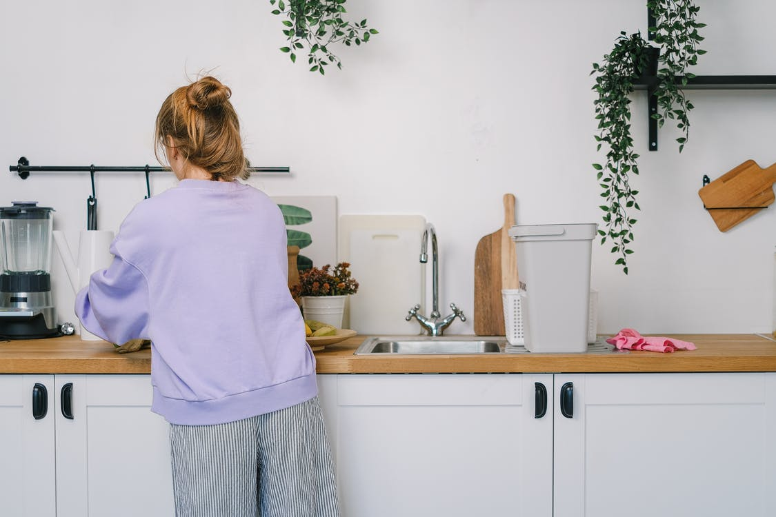 Woman standing at wooden counter in kitchen in daytime