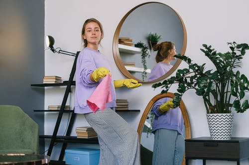 Positive female cleaning apartment in daytime
