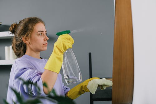 Side view of young calm female in protective latex gloves sprinkling liquid detergent from plastic bottle on mirror in light room