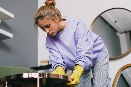 From below of young female in casual clothes and latex gloves standing and wiping table against mirrors in light room in daytime