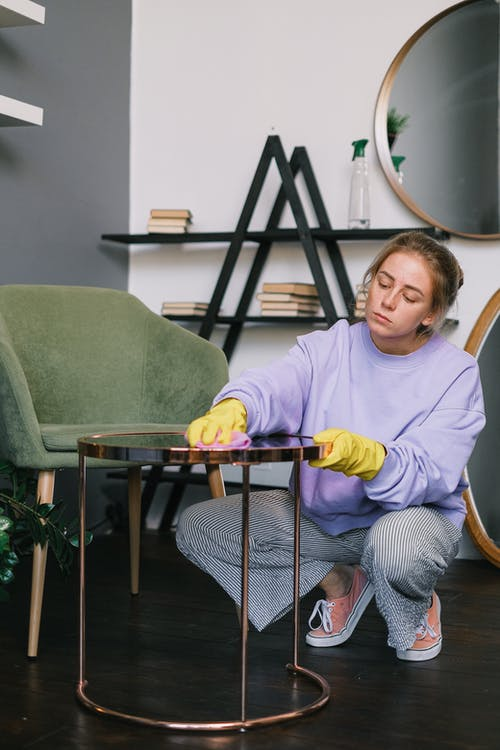 Female squatting down and wiping table in light room