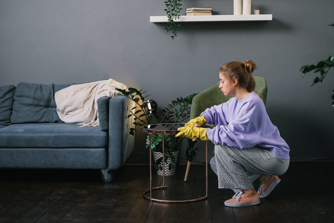 Side view of young female in latex gloves squatting down and wiping table in stylish living room in daytime