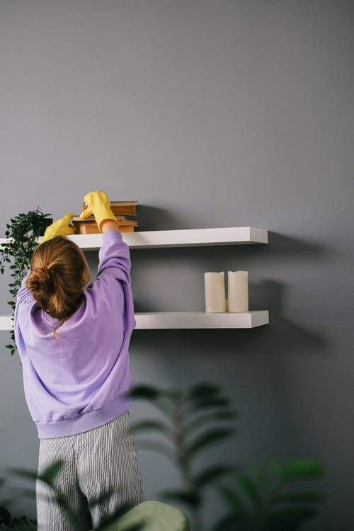 Back view of unrecognizable female in casual clothes and latex gloves standing and taking books while cleaning shelves in room with gray wall
