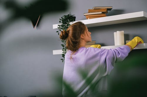 Young female wiping shelves in room with gray wall