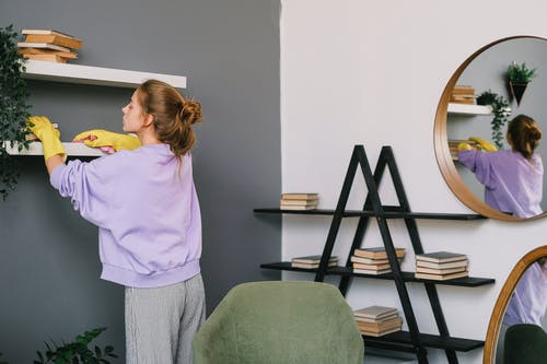 Woman Wearing Gloves Cleaning The Shelves