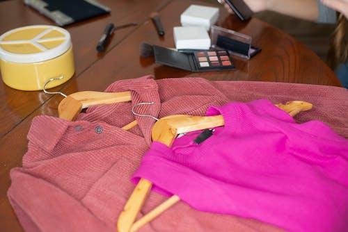 Бесплатное стоковое фото с вешалки для одежды, деревянный стол, косметические продукты