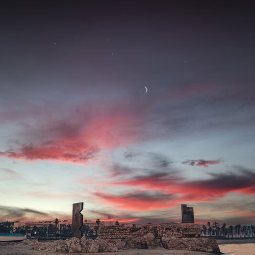 City Skyline Under Red and Blue Cloudy Sky