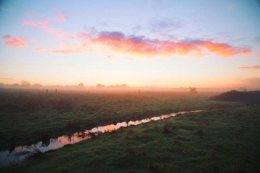 Water River Between Green Grass Field during Daytime