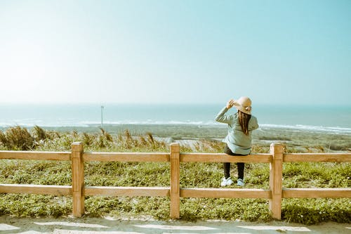 Back View of a Woman Sitting on a Wooden Fence