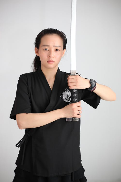 Serious Japanese female in black outfit with sword in hands looking at camera while standing on white background in studio