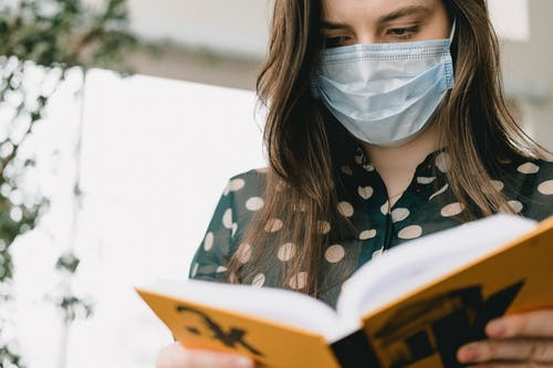 Crop young woman with long dark hair in elegant blouse and protective mask reading book in light library during COVID pandemic