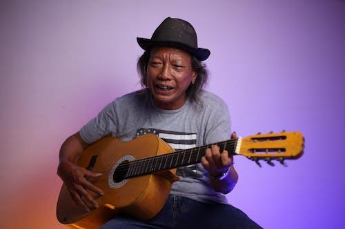 Mature Indian man playing guitar in studio