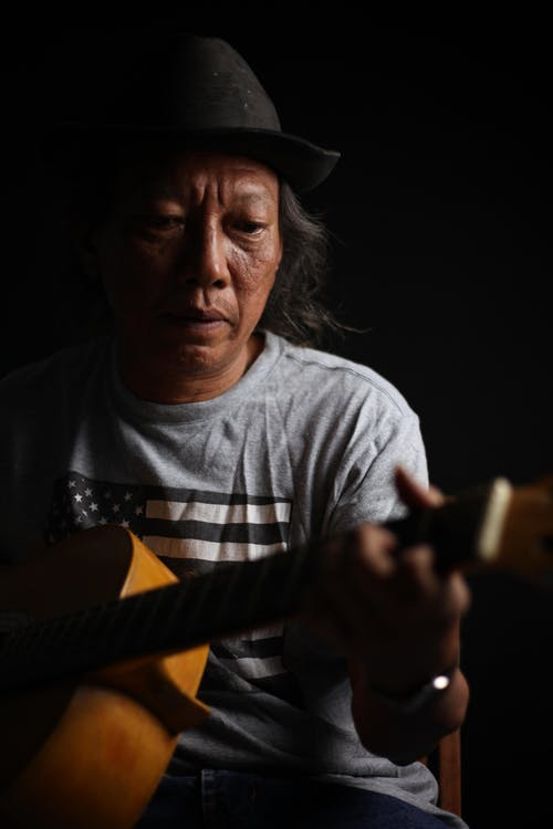 Senior Indian musician playing guitar in dark studio