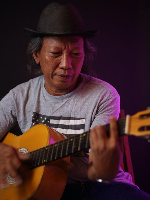 Skilled mature Native American man musician in hat and casual wear playing acoustic guitar while sitting on black background in studio with illumination