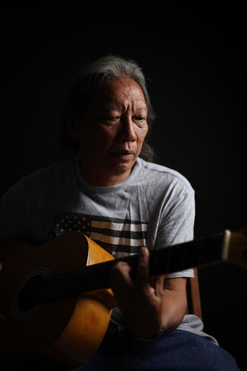 Senior Native American man playing guitar in darkness