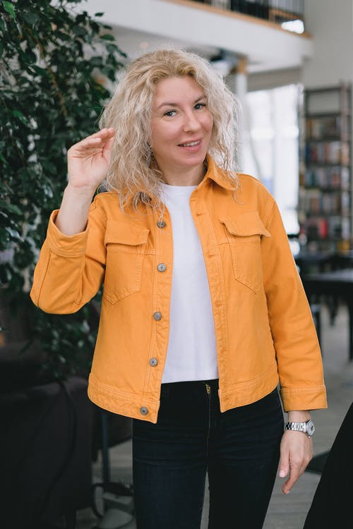 Positive adult female blogger with blond hair in casual clothes standing in light room and smiling while recording vlog