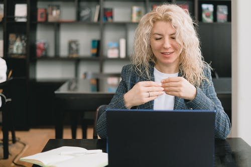Positive young female employee with curly blond hair in elegant clothes smiling while having video call via laptop sitting at table with notebook in modern office