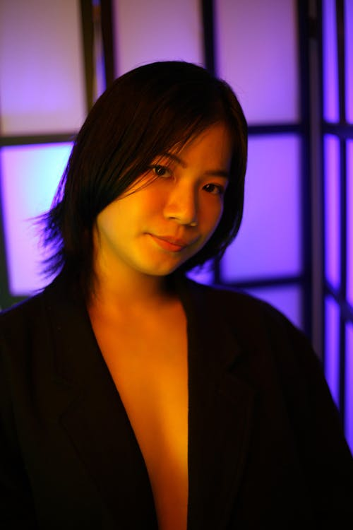 Delicate ethnic alluring female with short hairstyle looking at camera near violet light in studio
