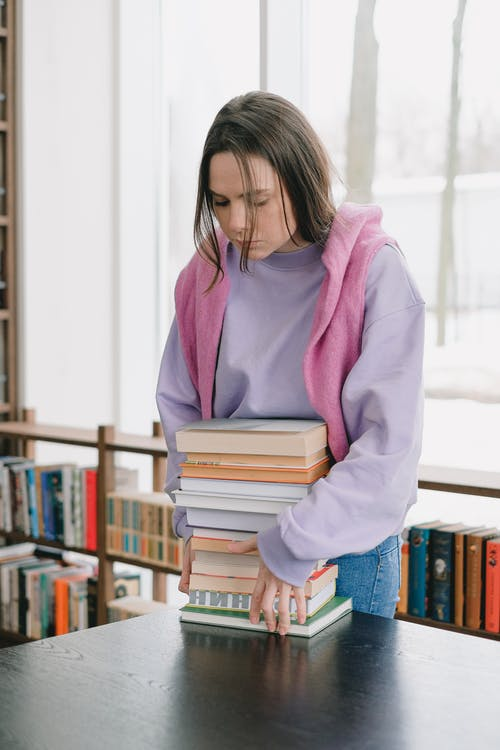 Woman in Purple Sweater Holding Books