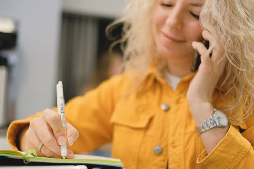 Content blond female employee writing notes while talking on cellphone on blurred background