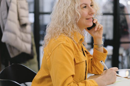 Side view of positive businesswoman sitting at table and writing notes while having conversation on mobile phone