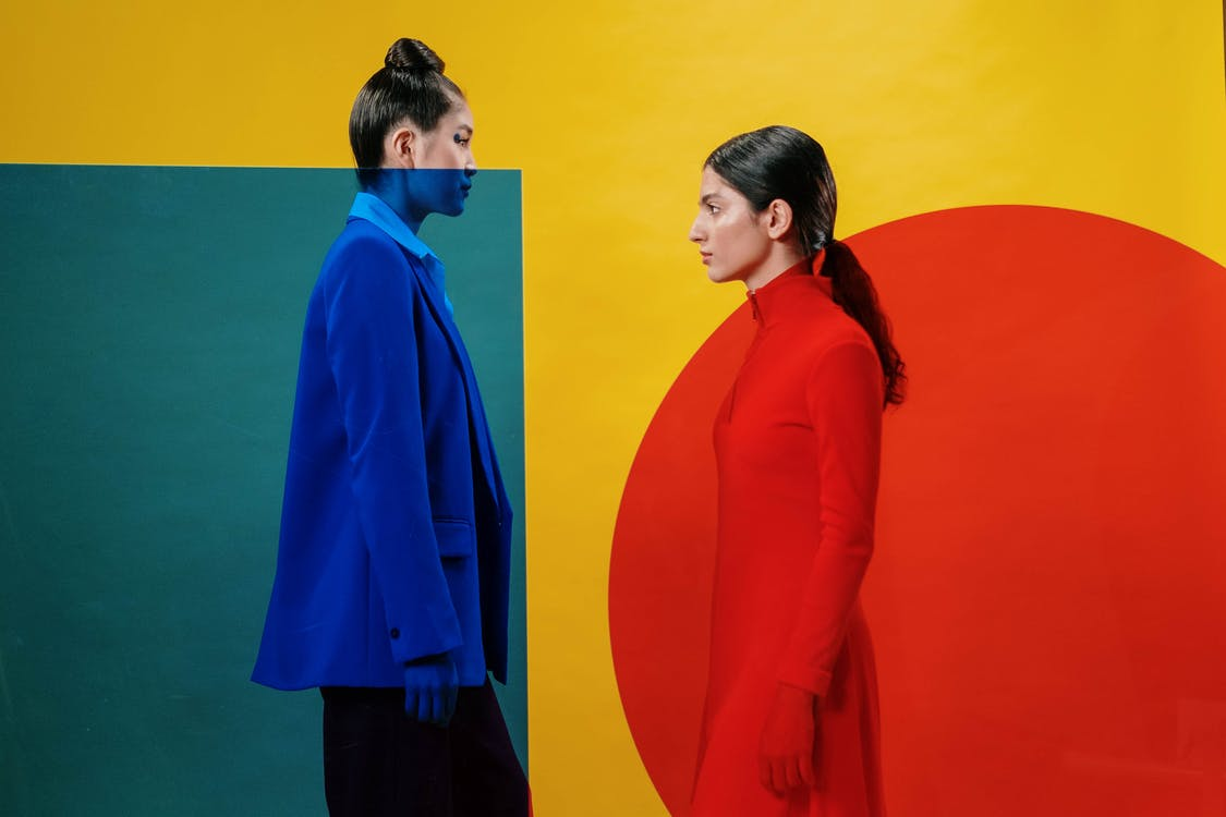 Woman in Red Long Sleeve Shirt Standing Beside Woman in Blue Coat