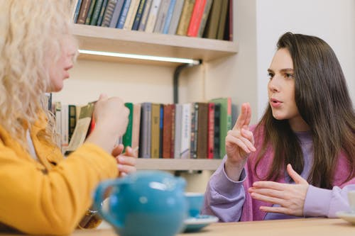 Side view of female friends sitting at table in university library and using sign language