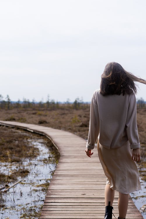 Carefree woman in casual stylish clothes walking on timber path
