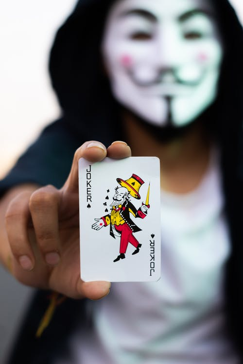 Person Holding Joker Playing Card