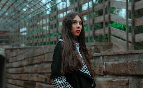 Woman in Black Long Sleeve Shirt Standing Near Brown Brick Wall