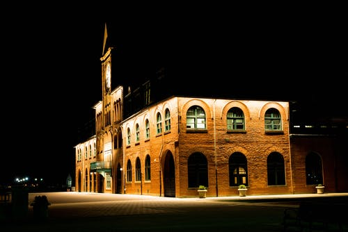 Brown Brick Building With Lights during Night Time