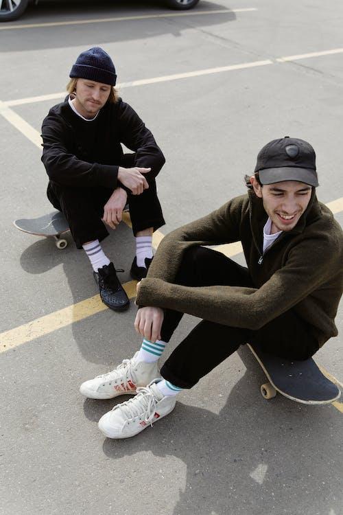 Men Sitting on their Skateboard