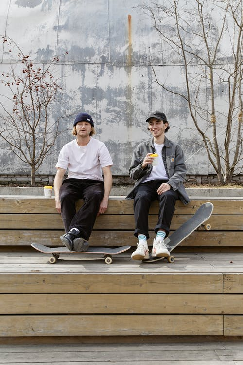 Two Men Sitting with Their Skateboards