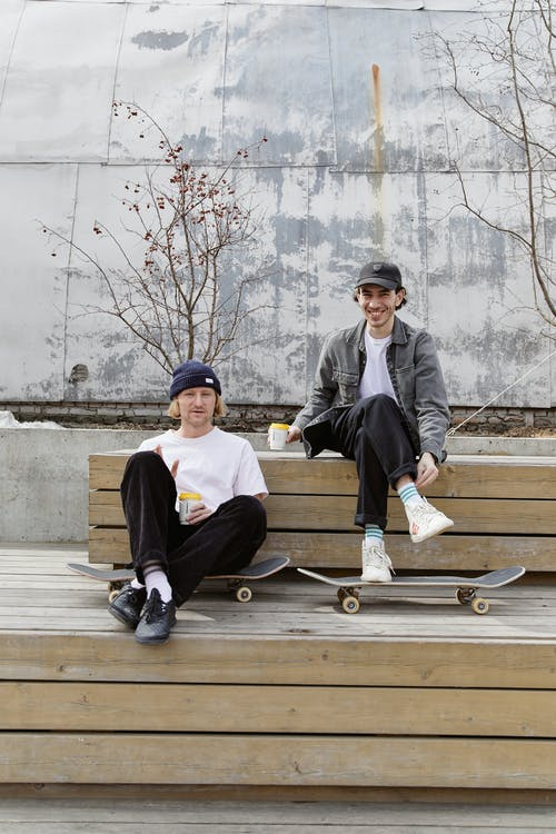 Two Best Friends Sitting Together with Their Skateboards