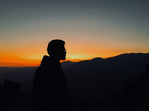 Silhouette of Man Standing during Sunset