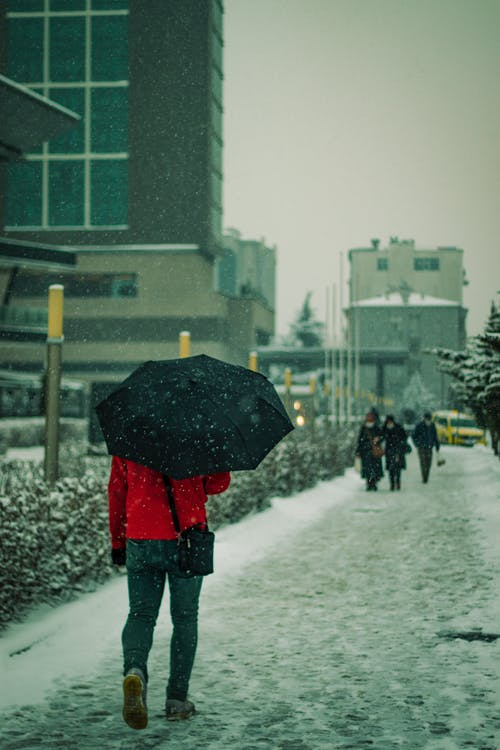A Person Walking and with an Umbrella