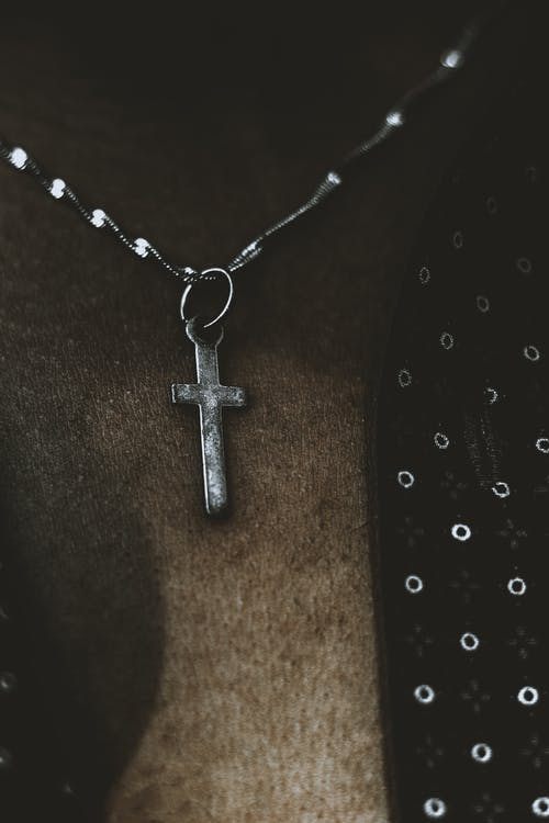 Silver Crucifix Pendant Necklace on Brown Wooden Table
