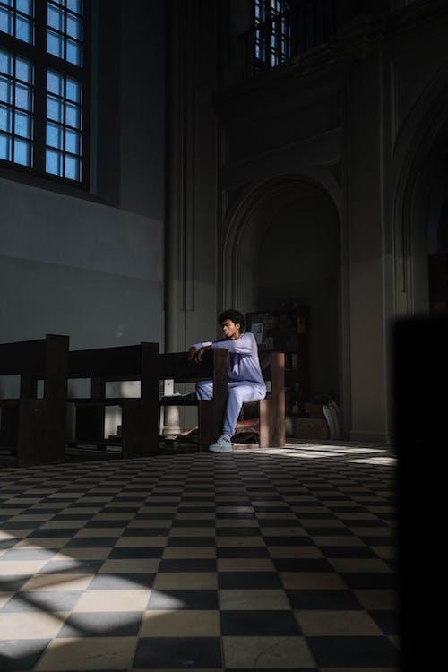 Man Sitting on a Church Pew