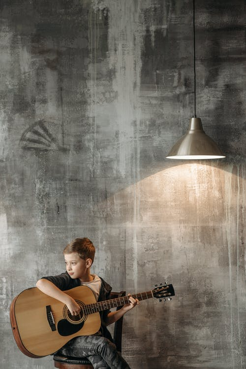 A Boy Playing Acoustic Guitar