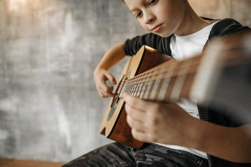 Close-Up Shot of a Boy Playing Acoustic Guitar