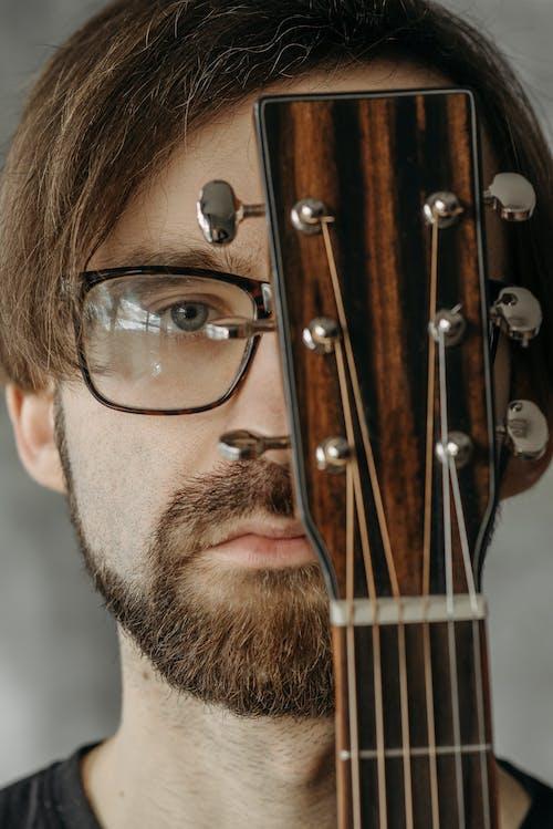 Man in Gray Shirt Playing Brown Acoustic Guitar