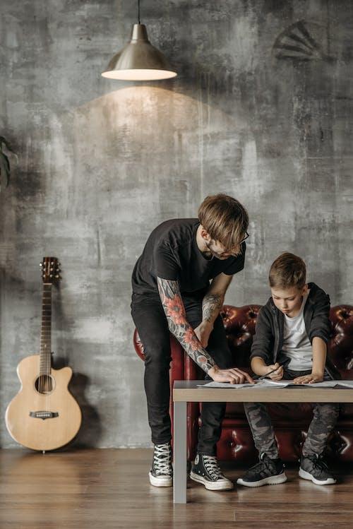 Gratis stockfoto met aan het studeren, akoestische gitaar, gitaarles