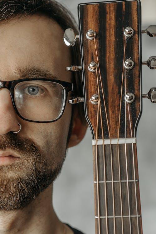 Close-Up Shot of a Serious Man and a Guitar