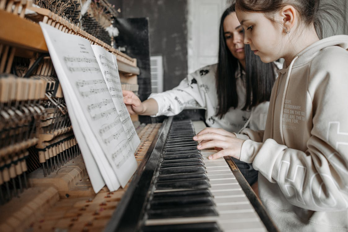 Girl in Beige Hoodie Playing Piano