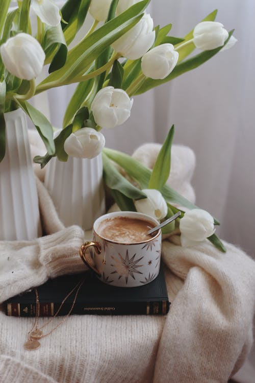 From above of ceramic cup of hot chocolate with spoon placed on book on warm sweater near vases with delicate white tulips