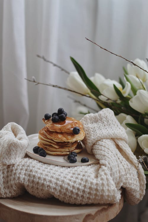 Stack of appetizing pancakes with syrup and blueberries served on plate and placed on stylish knitted sweater near bouquet of white tulips