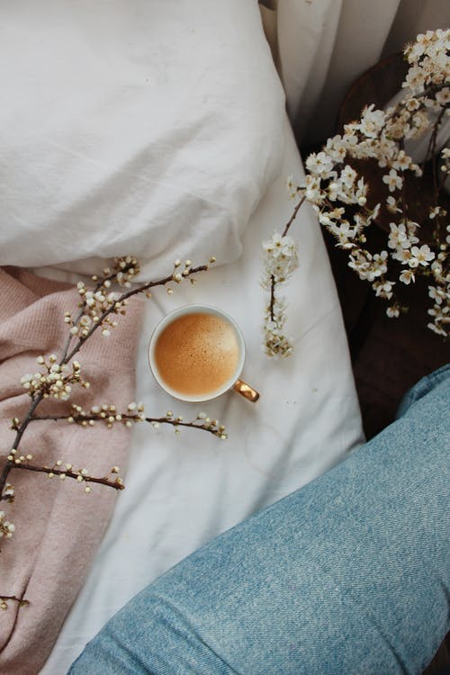 Top view of crop anonymous female in jeans sitting on comfortable bed near cup of aromatic hot cappuccino in cozy bedroom decorated with blooming branches