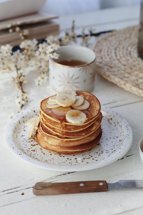 From above stack of yummy sweet pancakes topped with bananas and syrup served on plate on table with cup of tea in morning
